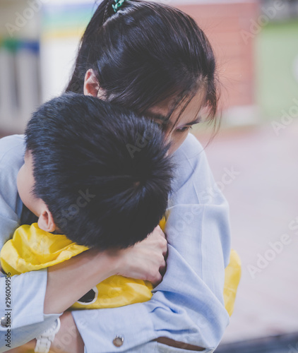 Fotomurales - Mother is holding an upset boy closely in her arm, for mother and parent caring concept.