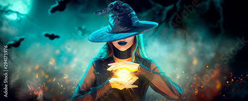 Fotomurales - Halloween Witch girl with making witchcraft, magic in her hands, spells. Beautiful young woman in witches hat conjuring. Spooky dark magic forest back