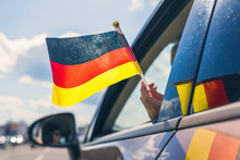 Fotomurales - Woman or Girl Holding Germany Flag from the open car window. Concept