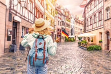 Fotomurales - Young asian woman tourist traveling with german flag near the famous half-timbered street in Nuremberg old town