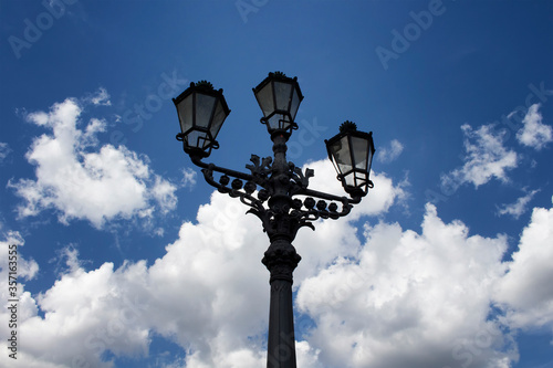 Fotomurales Old, historical, ornamental street lamp from bottom view in Berlin. Blue, cloudy sky makes the background. Symmetrical composition.
