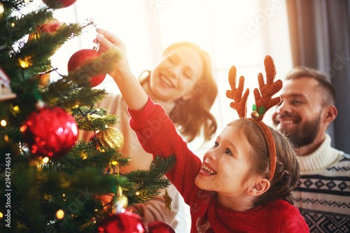 Fotomurales - happy family mother, father and child daughter decorate Christmas tree .
