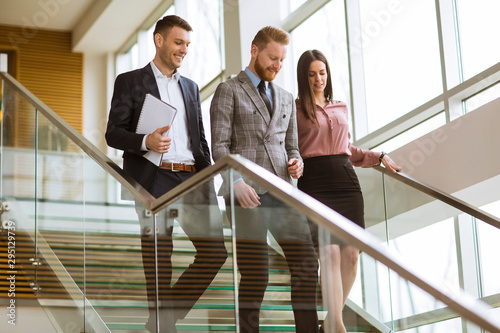Fotomurales - Business partners analyze the business results while walking down the stairs in modern office