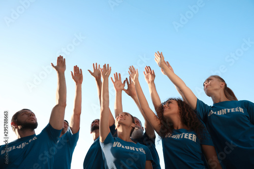 Fotomurales - Group of volunteers raising hands outdoors, low angle view