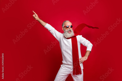 Fotomurales - Cool santa character aged man directing finger on advert banner wear sun specs knitted clothes isolated red background